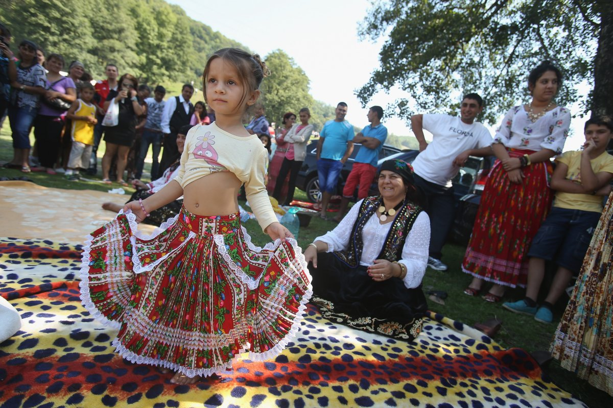 kalderash-rom-maria-mercedes-chiciu-3-shows-off-her-belly-dancing-skills-as-her-grandmother-exspertiza-dumitru-sitting-looks-on-at-the-field-near-the-bistrita-monastery-where-thousands